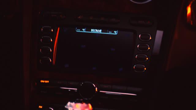 vídeos y material grabado en eventos de stock de close angle of car stereo or gps screen or monitor. burn-in. man driving bentley or luxury car. hand on gear shift. - radio