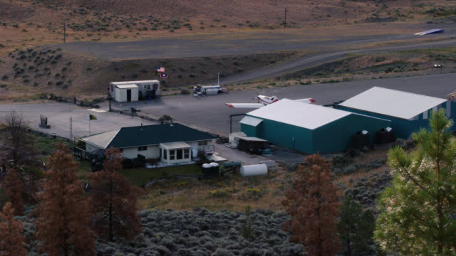 high angle down of private runway and hangars at yellowstone national park. small cessna airplane parked in front of hangars. another small airplane moves forward toward hangars. could have landed. trees visible. - 飛行機格納庫点の映像素材/bロール
