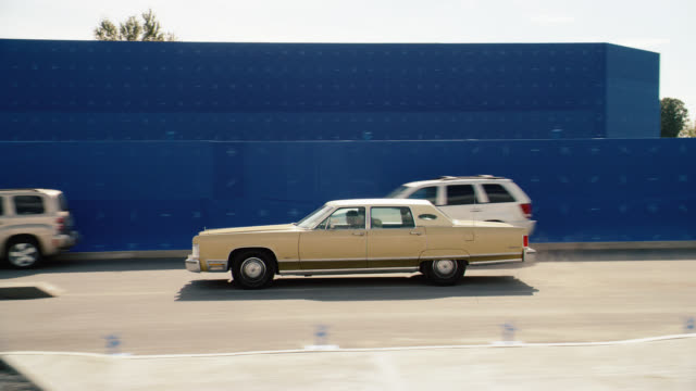 medium angle of cadillac car driving on street lined with blue screen. cars parked on curb. cadillac swerves to avoid obstacles in street. car stunt. - cadillac stock videos & royalty-free footage