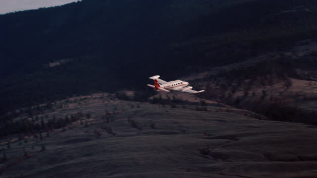 aerial of small private propeller airplane flying over wilderness, mountains, hills and fields. pine trees in woods or forest. - propeller video stock e b–roll