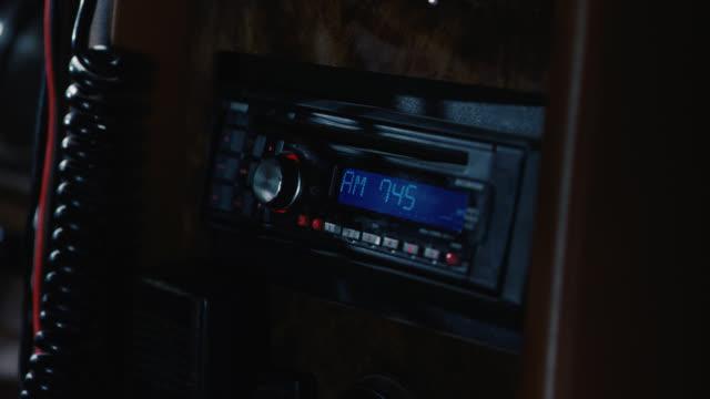 vídeos de stock, filmes e b-roll de close angle of hand adjusting cb radio system in car. series. - rádio eletrônico de áudio