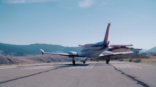 tracking shot of small private propeller airplane moving on runway of rural airport. dry landscape, mountains, hills or countryside. could be for landing or take-off. - プロペラ機点の映像素材/bロール