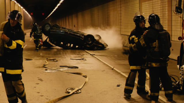 wide angle of firefighter or firemen at scene of car crash or accident inside tunnel. overturned 1968 citroen ds 21 in bg. fire truck visible. man with news cameraman or reporter filming scene. french police visible. - journalist stock videos & royalty-free footage