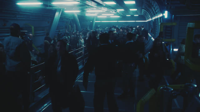 wide angle of crowd or mob of people running on platform. could be cargo bay of ship. panic. - terrified stock videos & royalty-free footage