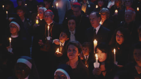 vídeos y material grabado en eventos de stock de medium angle of crowd of people with candles signing and mourning. cardinals or bishops visible amongst crowd. could be vatican. people start to panic and run away. fleeing. - cristianismo