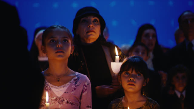 vídeos de stock, filmes e b-roll de medium angle of crowd of people with candles signing and mourning. cardinals or bishops visible amongst crowd. could be vatican. people start to panic and run away. fleeing. family stays behind. blue screen bg. - religião