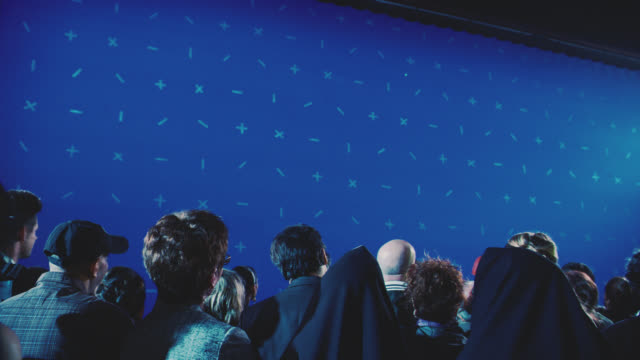 medium angle of people standing behind barricade looking up and blue screen. could be time square. people illuminated by lights. - chroma key stock videos & royalty-free footage