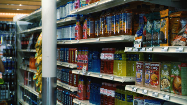 close angle of bottles of juice and sports drinks on shelves in grocery store or supermarket aisle. food. - 2009 stock videos & royalty-free footage