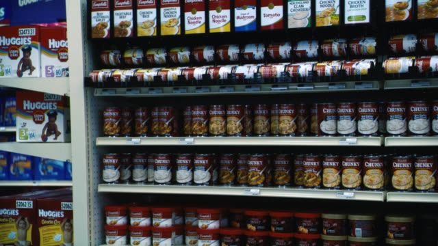 close angle of cans of soup on shelves in grocery store or supermarket aisle. food. - shelf stock videos & royalty-free footage