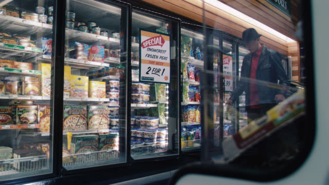 medium angle of freezers and frozen food section of grocery store. lights flashing, food falling from shelves, glass on door breaks. could be earthquake. - aisle stock videos & royalty-free footage