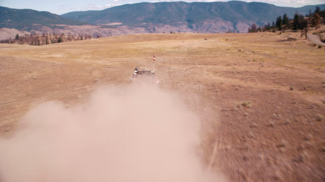 aerial of rv driving on dry, arid field surrounded by mountains and forests. could be national park. dirt or mountain road visible. fire and flames spewing from rear of rv. - dirt road stock videos & royalty-free footage