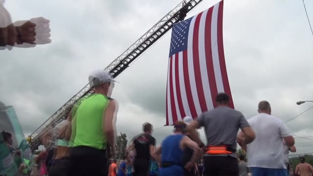 runners go under american flag right after start - querfeldeinrennen stock-videos und b-roll-filmmaterial