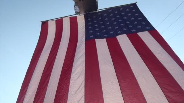 american flag raised at the starting line of running race - querfeldeinrennen stock-videos und b-roll-filmmaterial