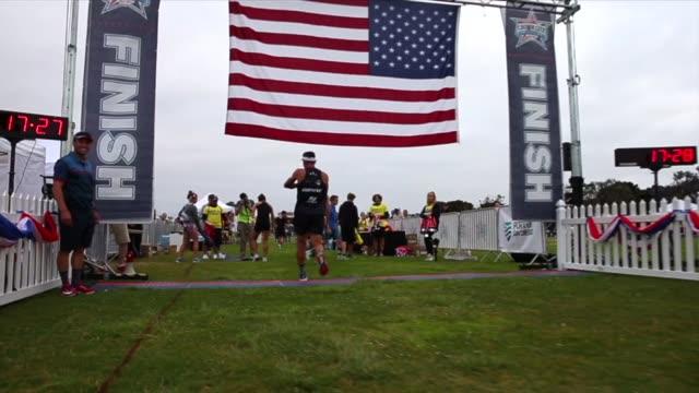 runner approaches finish line with american flag overhead - querfeldeinrennen stock-videos und b-roll-filmmaterial
