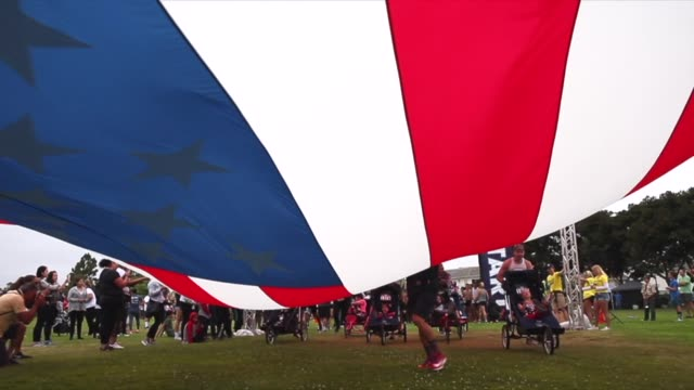 race starts american flag held parallel to the ground runners pushing baby joggers jogging strollers go under flag - querfeldeinrennen stock-videos und b-roll-filmmaterial