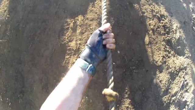 obstacle race one hand after the other gets racer down steep mud wall - tough mudder stock videos and b-roll footage