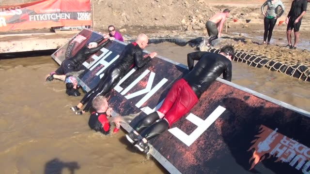 obstacle race teammates must work together to move through mud maze - querfeldeinrennen stock-videos und b-roll-filmmaterial