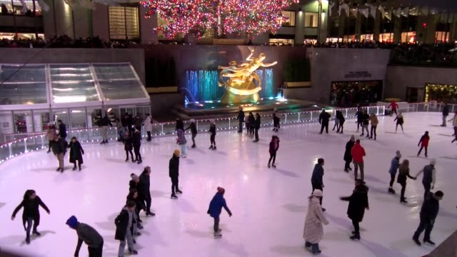 festive scene as ice skaters fill the rockefeller center rink, then camera pans up to show entire christmas tree - eislaufen stock-videos und b-roll-filmmaterial