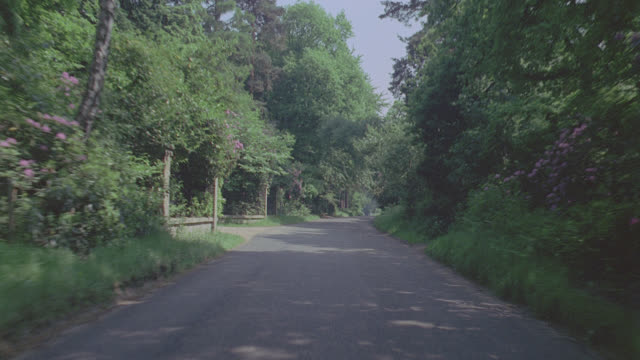 auto bg: london: day: straight back - along a country road; past house, bus stop; matching bg520-5,6 - moving process plate stock videos & royalty-free footage