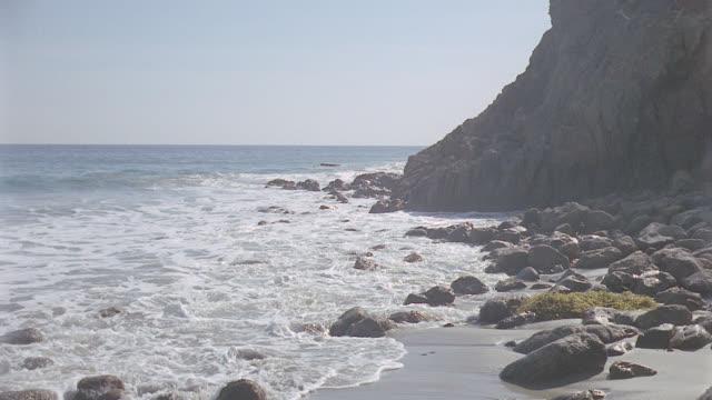 vídeos de stock e filmes b-roll de scenic: beach: lo setup location: malibu beach & surf shooting up beach r. rocks bg. shot at water's edge. - water's edge