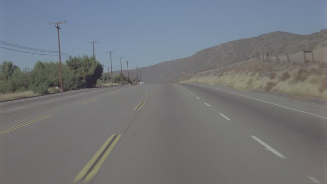 auto background: pch coast: day: straight forward traveling north on coast highway; light traffic, normal to 45mph. **mag light leak pulses throughout --- - light leak stock videos & royalty-free footage