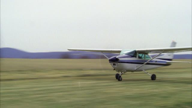 blue and white single engine cessna plane take off r-l from open field airplane autumn winter grey sky - elica parte di macchina video stock e b–roll