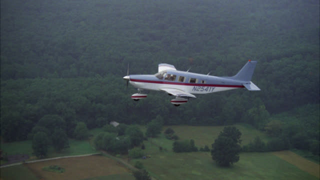aerial air-to-air tracking shot of culver's blue and white single engine plane with red stripe over fields and forest rural farmland see homes houses farms roads in bg  piper saratoga airplane cloudy hazy day multiple neg cuts - 1985 stock videos & royalty-free footage