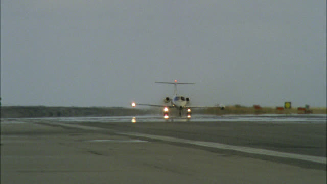 small jet private jet lear jet corporate jet in air airplane lights on white plane with red stripes take-off from small runway in front of lake river water sea negative is complete - 1985 stock videos & royalty-free footage