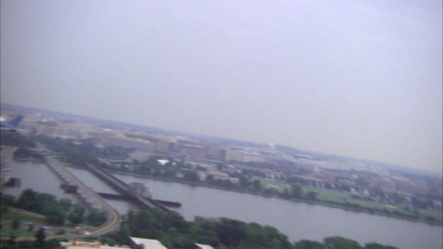 to-air tracking shot of culver's blue and white single engine plane with red stripe r-l over washington dc  piper saratoga airplane national monuments jefferson memorial washington monument  in bg plane flies over potomac river and fields multiple neg cut - river potomac stock videos & royalty-free footage