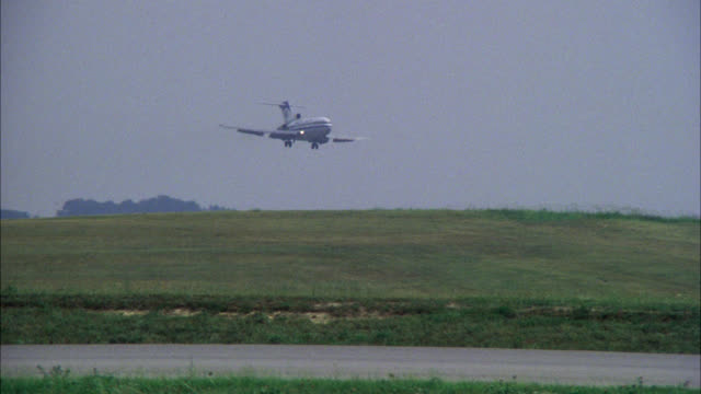 727 plane l-r    makes landing american trans air  ata  nd field commercial passenger jet    airplane lands cloudy hazy day - luftfahrzeug stock-videos und b-roll-filmmaterial