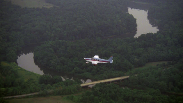 aerial air-to-air tracking shot down to culver's blue and white single engine plane with red stripe r-l over wooded area  and winding river farm fields forest piper saratoga airplane multiple neg cuts - 1985 stock videos & royalty-free footage