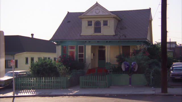 wide angle of two story victorian style house. two pay phones telephones located in front. yellow house green picket fence.  brown sedan drives l-r and parks in front. middle class. residential areas. - wide angle stock videos & royalty-free footage