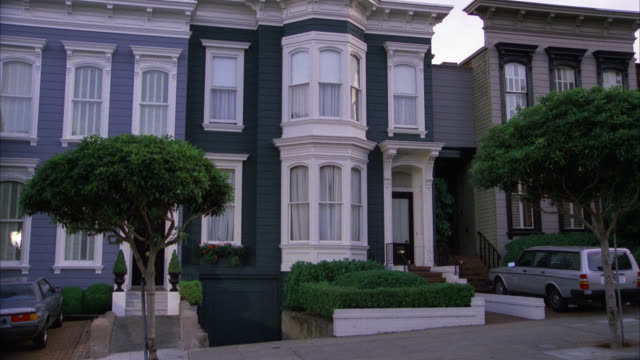 est harrison's victorian style house / grey gray and white / no camera move / townhouse  side by side row house similar to the cosby house  two story  volvo station wagon parked in driveway  few cars drive by trees in front - zweistöckiges wohnhaus stock-videos und b-roll-filmmaterial