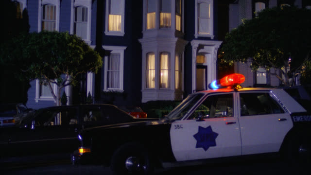 "est harrison's victorian style grey gray and white two story middle class  house townhouse with police car parked in front  police car says ""sfpd""     red lights on cmi to first floor window  lights on - san francisco california stock videos & royalty-free footage"