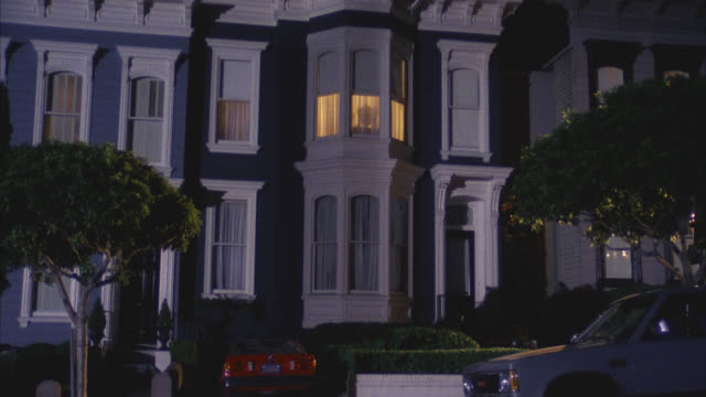 est harrison's victorian style grey gray and white house townhouse middle class two story   cmi to upstairs window     only one light on bmw parked in driveway - zweistöckiges wohnhaus stock-videos und b-roll-filmmaterial