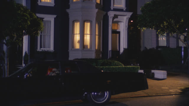 est harrisons victorian style grey gray and white house two story middle class   cmi over and past harry's brown cadillac and zooms in window with lights on / camera pulls back and zooms in several times - zweistöckiges wohnhaus stock-videos und b-roll-filmmaterial