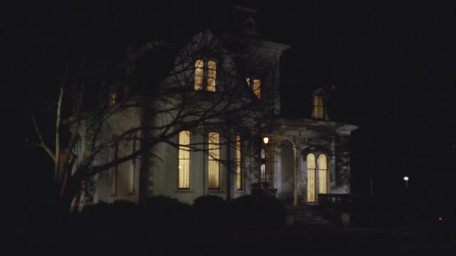 wide angle of upper class victorian gothic white three story mansion house at night. see inside lights turned on. see tree in front yard. - upper class stock videos & royalty-free footage
