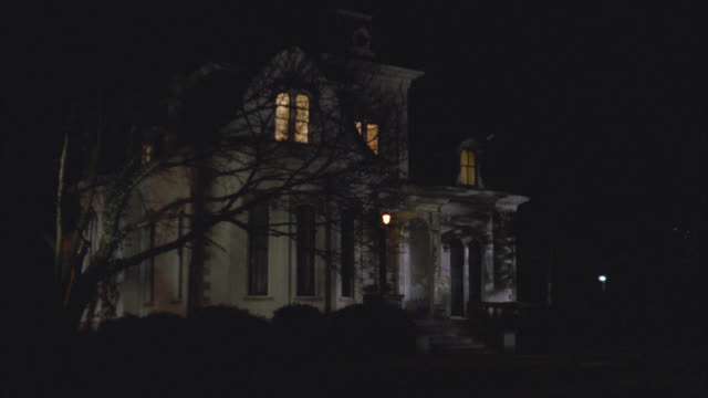 wide angle of upper class victorian gothic white three story mansion house at night. see inside lights turned on, then one light upstairs turns off. see tree in front yard. - 1992 stock videos & royalty-free footage