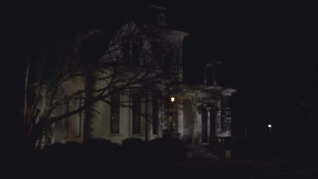 wide angle of upper class victorian gothic white three story mansion house at night. all inside lights are off. see lights in two rooms turn on one after another. see tree in front yard. - 1992 stock videos & royalty-free footage