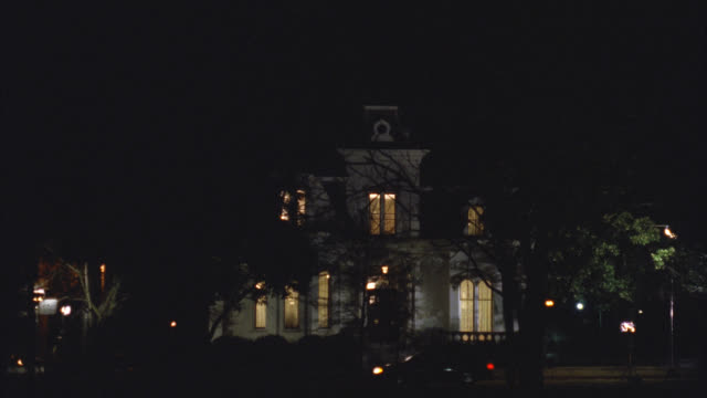 wide angle of upper class victorian gothic white three story mansion house at night. all inside lights are on. see tree in front yard. see car drive by right to left. - 1992 stock videos & royalty-free footage