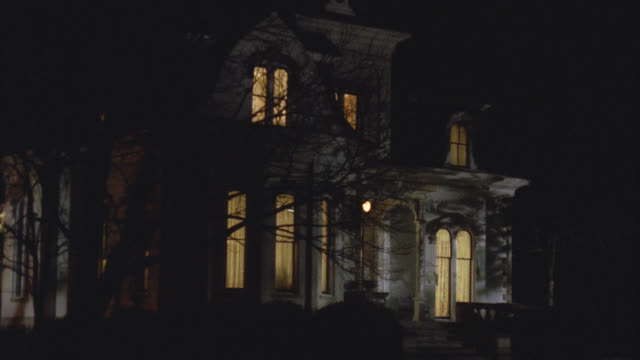 wide angle of upper class victorian gothic white three story mansion house at night. see interior lights on. - 1992 stock videos & royalty-free footage