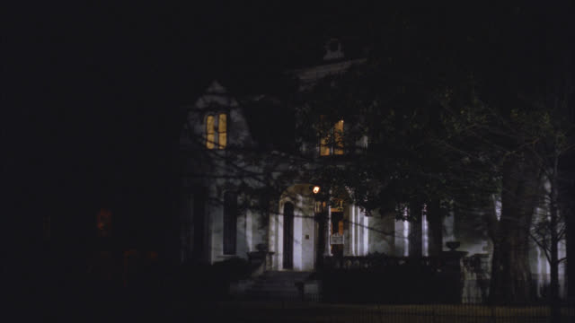 wide angle of upper class victorian gothic white three story mansion house at night. see trees in front yard. see lights on upstairs. - 1992 stock videos & royalty-free footage