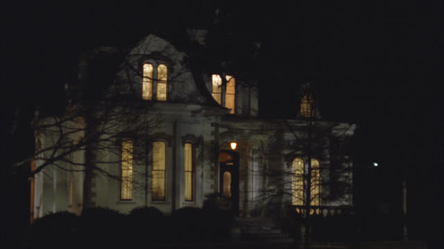wide angle of upper class victorian gothic white three story mansion house at night. see car drive by right to left and then lights in house turn off one by one. - 1992 stock videos & royalty-free footage