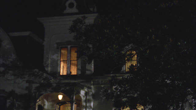 medium angle of upper class victorian gothic white three story mansion house at night. see upstairs light turn off. - 1992 stock videos & royalty-free footage