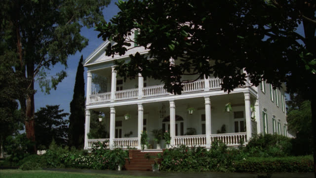 building      house   large white frame two story     railings both floors lawn     hedges   trees    zooms into porch area front door - zweistöckiges wohnhaus stock-videos und b-roll-filmmaterial