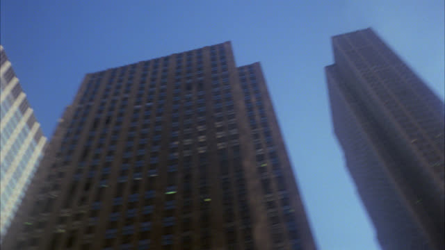 stockvideo's en b-roll-footage met up angle to see circular turning pan of tops of skyscrapers buildings   this works for someone's pov looking up and turning around in a circle   2nd take  camera is on a slant see radio city music hall skyscraper - radio city music hall
