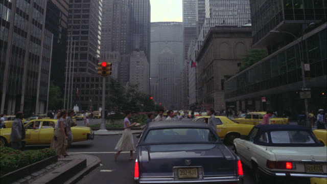 est new york     ls street   pan up to sky between tops of skyscrapers     pan down to street    buildings   skyscraper   park avenue storm clouds above grand central station in bg - 1979 stock videos & royalty-free footage