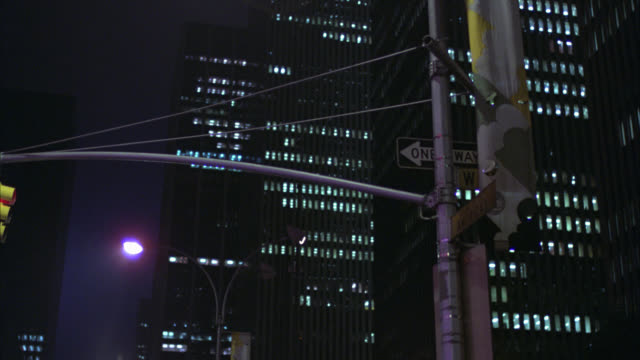 est city street with traffic and then pan right and over and up to high rise office building        all lights on  also has clip of pedestrians crossing street - 1980 stock videos & royalty-free footage