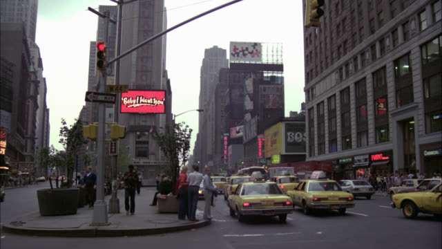 "times square  lots of traffic  zoom into buildings  lots of neon signs sign says ""featuring the hit single ..."" bldg says ""quasimodo"" - anno 1979 video stock e b–roll"