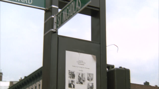 up angle to street sign that reads w 125th street dr martin luther king jr blvd     camera pans down and right to street corner with much activity people pedestrians traffic see storefronts   predominantly black people - boulevard video stock e b–roll